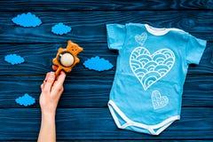 Nowonarodzony dziecka ` s sen pojęcie Stawiać dziecka łóżko Dziecka bodysuit blisko chmurnieje i cbaby akcesoria na błękitny drew Obraz Stock