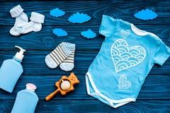 Nowonarodzony dziecka ` s sen pojęcie Stawiać dziecka łóżko Dziecka bodysuit blisko chmurnieje i cbaby akcesoria na błękitny drew Obraz Royalty Free