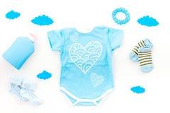 Nowonarodzony dziecka ` s sen pojęcie Stawiać dziecka łóżko Dziecka bodysuit blisko chmurnieje i cbaby akcesoria na bielu Fotografia Stock