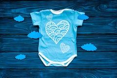 Nowonarodzony dziecka ` s sen pojęcie Stawiać dziecka łóżko Dziecka bodysuit blisko chmurnieje na błękitnego drewnianego tła odgó Fotografia Stock