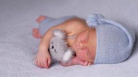 Nowonarodzony dziecko w czapeczce śpi na stronie zbiory wideo