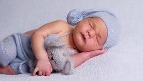 Nowonarodzony dziecko w czapeczce śpi na stronie zdjęcie wideo