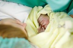 Nowonarodzony dziecko zawijaj?cy w koc po narodziny Macierzysty patrze? pierwszy raz na nowonarodzonej c?rce zdjęcie stock