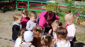 NOWOSIBIRSK, RUSSLAND - 16. August 2017: Im Kindergarten die Frau, die draußen mit den Kindern, aktive Spiele spielt stock video