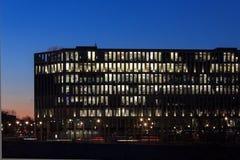 Nowożytna budynek biurowy fasada, ludzie pracuje przy nocą Obraz Stock