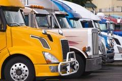 Nowożytna kolor żółty ciężarówka na przedpolu inny semi przewozi samochodem Obraz Stock