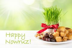 Nowruz holiday concept - grass, baklava sweets, nuts and seeds. Copy space stock photography
