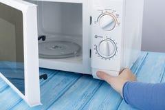Nowy biały mikrofala piekarnik na błękitnej drewnianej powierzchni dla ogrzewać, Fotografia Royalty Free