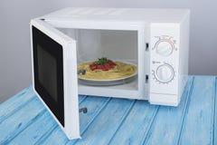 Nowy biały mikrofala piekarnik na błękitnej drewnianej powierzchni dla ogrzewać, Obraz Stock