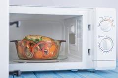 Nowy biały mikrofala piekarnik na błękitnej drewnianej powierzchni dla ogrzewać, Obrazy Royalty Free