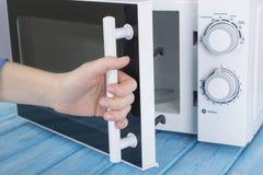 Nowy biały mikrofala piekarnik na błękitnej drewnianej powierzchni dla ogrzewać, Zdjęcie Stock