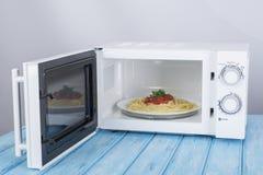 Nowy biały mikrofala piekarnik na błękitnej drewnianej powierzchni dla ogrzewać, Fotografia Stock