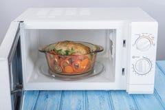 Nowy biały mikrofala piekarnik na błękitnej drewnianej powierzchni dla ogrzewać, Obraz Royalty Free
