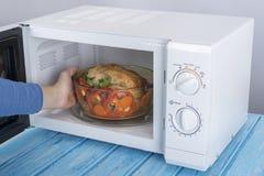 Nowy biały mikrofala piekarnik na błękitnej drewnianej powierzchni dla ogrzewać, Zdjęcia Stock