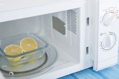 Nowy biały mikrofala piekarnik na błękitnej drewnianej powierzchni dla ogrzewać, Obrazy Stock