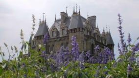 Nowy budynek stylizował jak średniowieczny kasztel, dzień, lato, kwiatu łóżko z błękitnymi kwiatami zdjęcie wideo