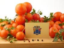 Nowy - bydło flaga na drewnianym panelu z pomidorami odizolowywającymi na wh Zdjęcie Royalty Free