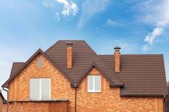 Nowy cegła dom z modularnym kominem, Dryluje Pokrytego metalu Dachową płytkę, plastikowych okno i podeszczową rynnę, fotografia stock