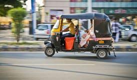 Nowy Delhi, India - 20 mogą 2018: panning młody indyjski riksza kierowca w ulicie z pasażerem w tradycyjnym sari riksza fotografia stock