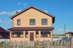 Nowy ludnościowy dom na wsi za starym ogrodzeniem Zdjęcia Stock
