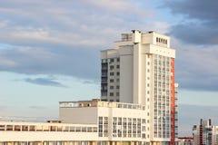 Nowy nowożytny blokowy multistory dom na zmroku - niebieskiego nieba tło w cztery kolorach: czerwień, pomarańcze, popielaty i bia Fotografia Stock