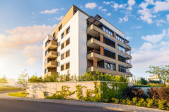 Nowy nowożytny blok mieszkalny w zielonym terenie z niebieskim niebem Obraz Stock