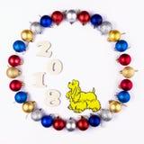 Nowy Rok, Bożenarodzeniowy wianek Kolorowe piłki z Żółtym psem Odgórny widok Fotografia Stock