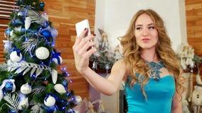 Nowy Rok fotografia przy telefonem komórkowym, dziewczyna robi selfie, świąteczny przyjęcie przy choinki piękną dziewczyną używa  zbiory wideo