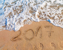 Nowy Rok 2017 jest nadchodzącym pojęciem pisać na piaskowatej plaży Fotografia Stock