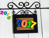 Nowy rok 2017 postacie w obrazek ramie na białym drewnianym tle Fotografia Royalty Free