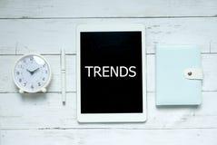 Nowy trend technologii biznesu pojęcie Odgórny widok zegar, pióro, notatnik i pastylka pisać z trendami na białym drewnianym tle, obrazy stock