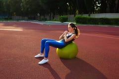 Noyau strengthing de femme sportive de brune avec la boule d'ajustement au stad Images libres de droits