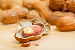 Noyaux d'arachides avec les shelles criqués sur en bois Image libre de droits