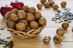 Nozes em uma cesta, em maçãs e em sementes de abóbora em um fundo da árvore fotografia de stock royalty free