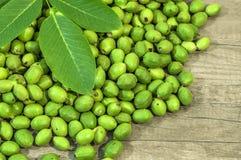 Nozes novas muito verdes nas cascas na mesa de cozinha com folhas verdes Foto de Stock