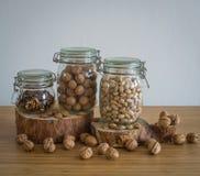 Nozes, nozes descascadas, pistaches, nozs do Brasil no frasco de vidro no suporte de madeira Foto de Stock Royalty Free