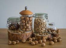 Nozes, nozes descascadas, pistaches, nozs do Brasil no frasco de vidro no suporte de madeira Imagem de Stock Royalty Free