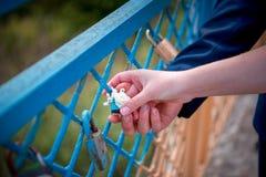 Nozze blu della serratura e le mani del ` s delle coppie fotografia stock libera da diritti