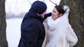 Nozze di inverno, conversazione piacevole felice e di risata delle persone appena sposate giorno gelido e nevoso, sulla banca del archivi video