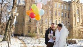 Nozze di inverno, persone appena sposate felici e di risate con dei i palloni luminosi e colorati multi giorno nevoso soleggiato, stock footage