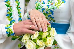 Nozze, mani del ` s della sposa con le fedi nuziali su un mazzo di nozze fotografia stock libera da diritti
