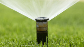 Nozzle automatic watering system against. A background of green grass royalty free stock photography