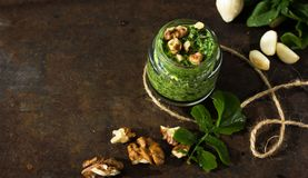 Pesto cooking freshly grounded pesto sauce in a glass jar front view. NPesto cooking freshly grounded pesto sauce in a glass jar front view Royalty Free Stock Image