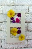 Photo frame and summer flowers in the interior against a white wall of kerpich, stock photos