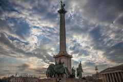Heroes square Hosok Tere in Budapest, Hungary, at Sunset, with tourists climbing the main statue and column Royalty Free Stock Photos
