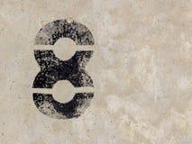 Nr. acht 8 auf Betonmauerhintergrund Stockbild