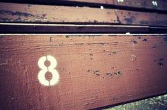 Nr. acht gemalt auf einem alten hölzernen Sitz Lizenzfreie Stockfotografie