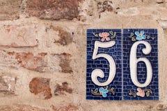 Nr. 56 auf der braunen Backsteinmauer eines Hauses Stockbilder