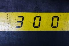 Nr. 300 auf gelbem Streifen und schwarzem Hintergrund Stockbild