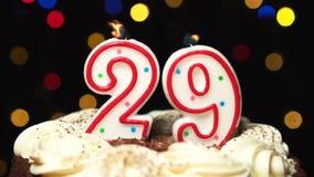 Nr. 29 auf Kuchen - achtundzwanzig Geburtstagskerze Burning - brennen Sie heraus am Ende durch Farbe unscharfer Hintergrund stock footage
